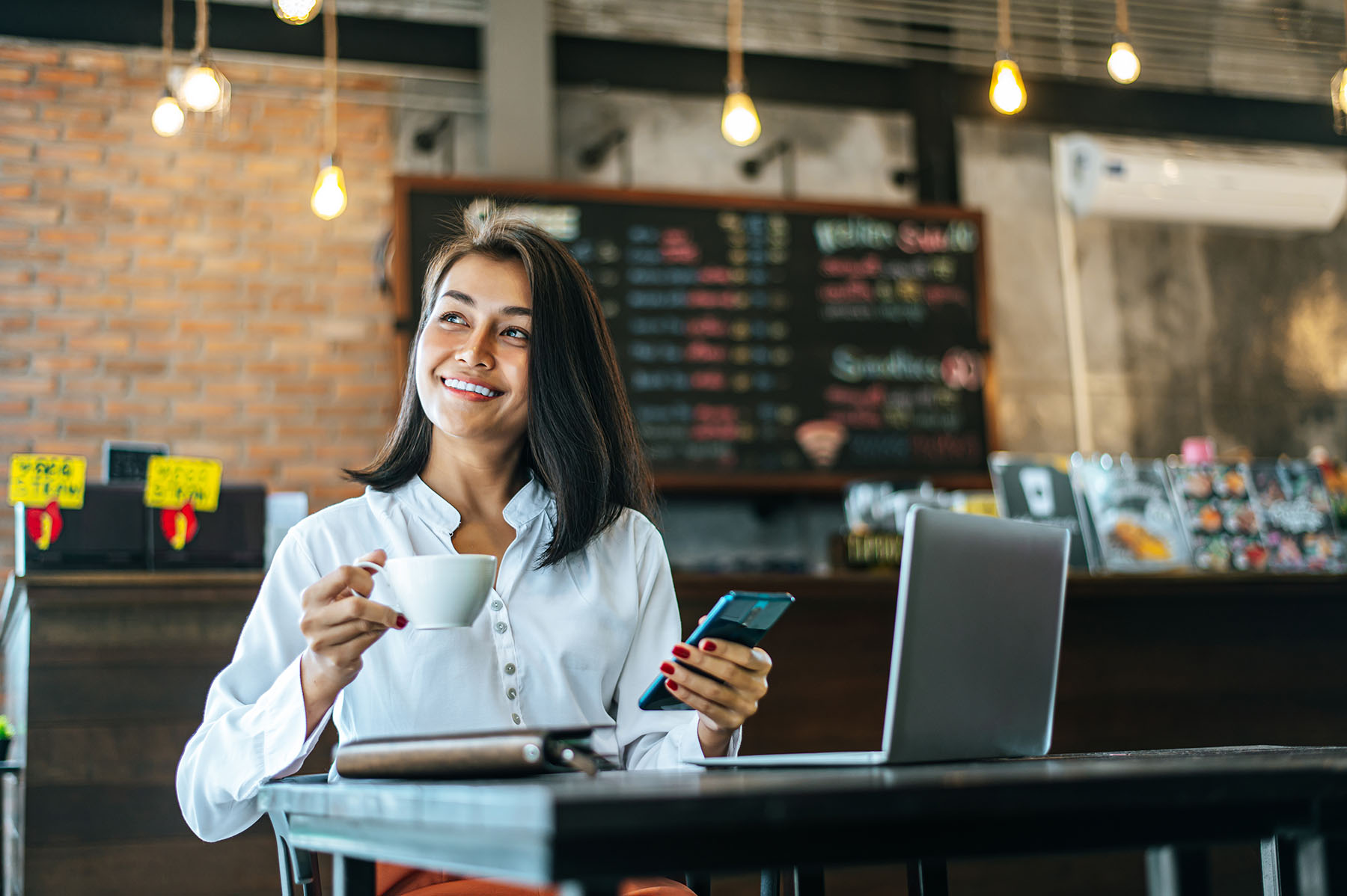 Woman Sitting Happily Working With A Smartphone In A Coffee Shop